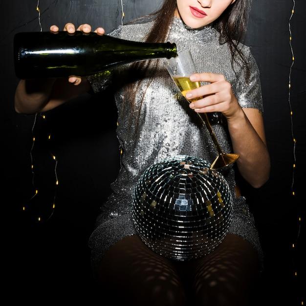 Dame gietende champagne in glas dichtbij discobal Gratis Foto
