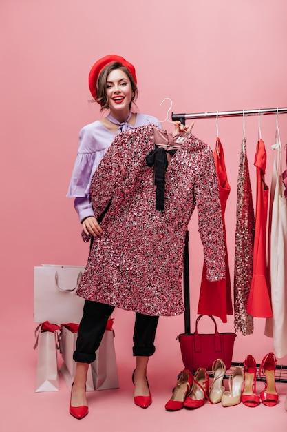 Dame in broek en blouse houdt jurk met pailletten. vrouw poseren met pakketten tijdens het winkelen op roze achtergrond. Gratis Foto