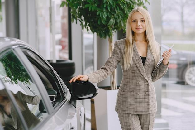 Dame in een autosalon. vrouw die de auto koopt. elegante vrouw in een bruin pak. Gratis Foto