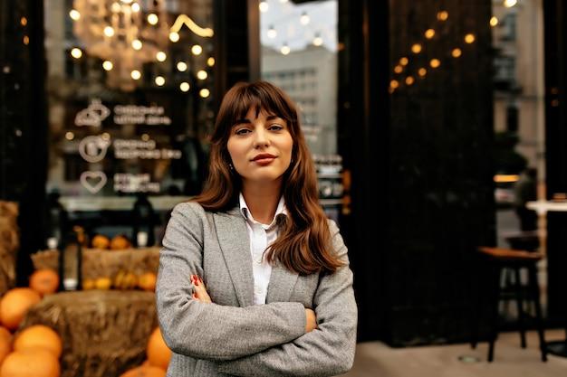 Dame in grijs pak glimlachend in de camera op achtergrond van stijlvolle café met verlichting. Gratis Foto