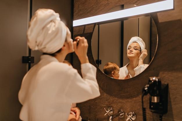 Dame in handdoek op haar hoofd doet oogmake-up, kijkt in badkamerspiegel en houdt baby vast. Gratis Foto