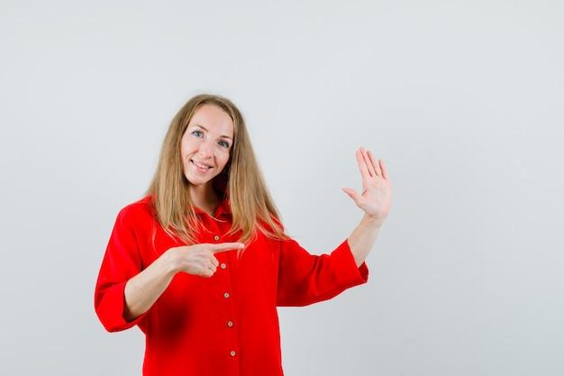 Dame in rood overhemd wijst opzij, toont palm en ziet er vrolijk uit, Gratis Foto