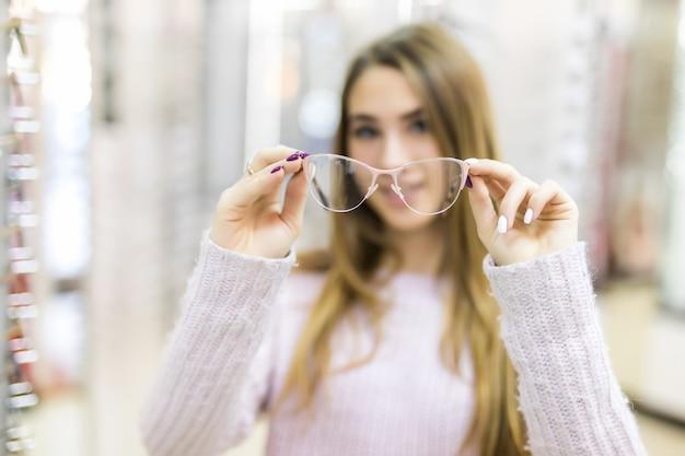 Dame met lang goudkleurig haar en modellook tonen het verschil in bril in professionele winkel Gratis Foto