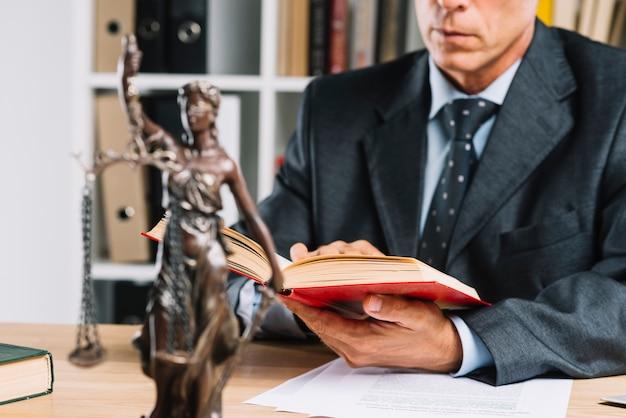 Dame van rechtvaardigheid voor de wetboek van de advocaatlezing in de rechtszaal Premium Foto