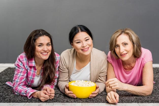 Dames die op vloer popcorn eten Gratis Foto