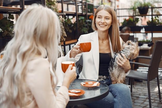 Dames drinken koffie. vrouwen aan de tafel. vrienden met een schattige hond. Gratis Foto