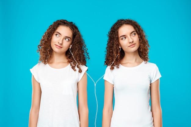 Dames tweeling luisteren muziek in de koptelefoon, glimlachend over blauw. Gratis Foto