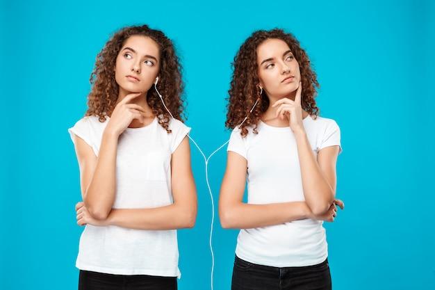 Dames tweeling luisteren muziek in koptelefoon, denken over blauw. Gratis Foto