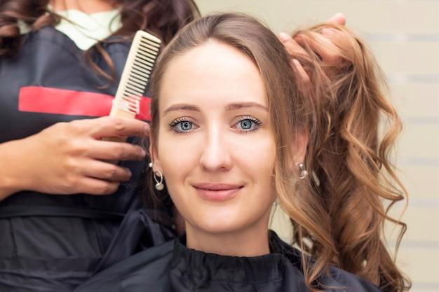 Dameskapper, schoonheidssalon. close up van een kapper die een kapsel doet. Premium Foto