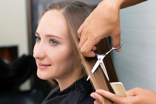 Dameskapper, schoonheidssalon. professionele stylist knipt vrouwelijk haar in salon Premium Foto
