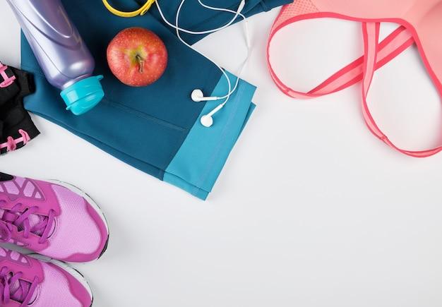 Dameskleding voor fitness, fles, hoofdtelefoons en sneakers Premium Foto