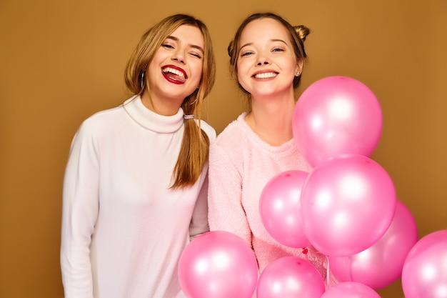 Damesmodellen met roze luchtballonnen op gouden muur Gratis Foto