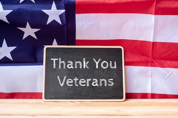 Dank u veteranen tekst geschreven in krijtbord met vlag van de verenigde staten Premium Foto