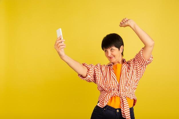 Dansen. portret van senior vrouw in stijlvolle outfit, kleding geïsoleerd op gele studio achtergrond. tech en vreugdevolle ouderen levensstijl concept. trendy kleuren, voor altijd jeugd. copyspace voor uw advertentie. Gratis Foto
