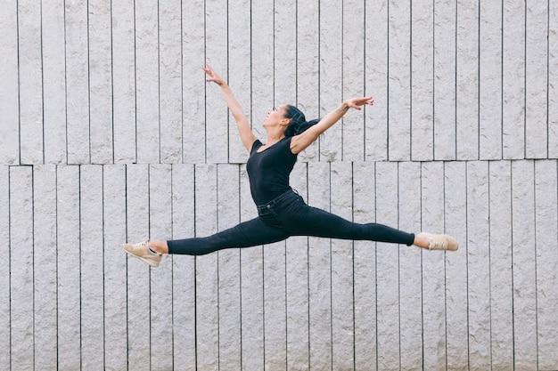 Danser die tussen verschillende rassen geïsoleerd op een grijze muur springen Premium Foto