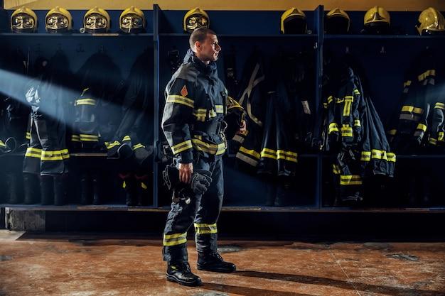 Dappere jonge brandweerman permanent in brandweerkazerne in beschermende uniform en helm onder oksel te houden. Premium Foto
