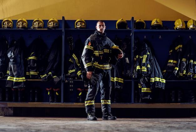 Dappere jonge brandweerman permanent in brandweerkazerne in beschermende uniform en helm te houden. Premium Foto