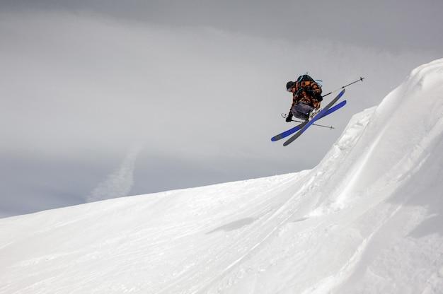 Dappere skiër stijgt van de grond terwijl hij van de besneeuwde bergen glijdt Premium Foto