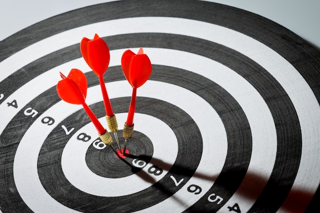 Dartpijl raakt in het doelcentrum van dartbord. concept van het succes Premium Foto