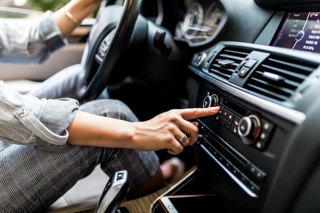 Dashboard van de auto. radio close-up. vrouw stelt radio in tijdens het autorijden Gratis Foto