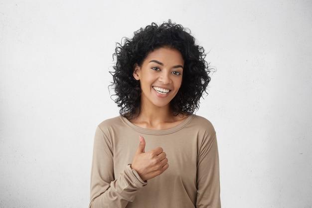 Dat vind ik leuk. goed gedaan. gelukkig jong donkerhuidig vrouwtje dat een casual t-shirt met lange mouwen draagt, duimen omhoog maakt en vrolijk lacht, haar steun en respect toont aan iemand. lichaamstaal Gratis Foto