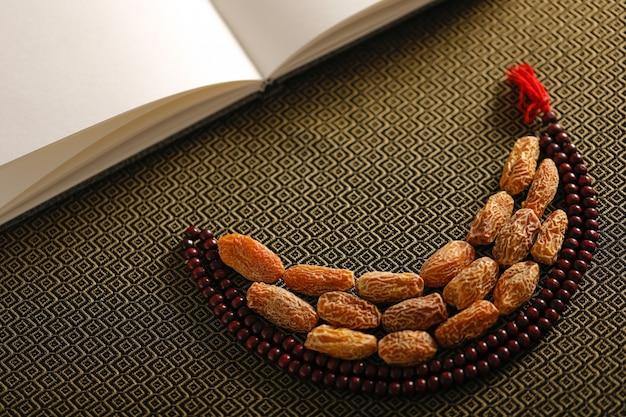 Datumvruchten met een islamitische gebedsparels op een artistieke achtergrond Premium Foto
