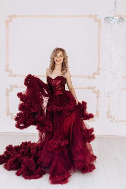 De aanbiddelijke vrouw in rode kleding van bourgondië stelt in een heldere luxeruimte met grote kroonluchter Gratis Foto
