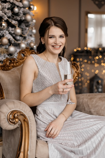 De aanbiddelijke vrouw in zilveren kleding zit vóór een kerstboom met een champagneglas in haar hand Gratis Foto