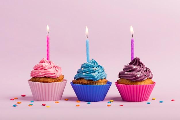De aangestoken kaarsen over de muffins met kleurrijk bestrooit op roze achtergrond Gratis Foto