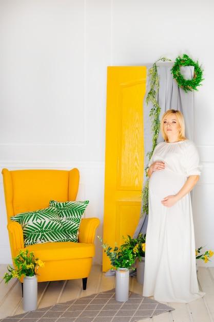 De aanstaande moeder in een witte jurk houdt haar armen in haar buik Premium Foto