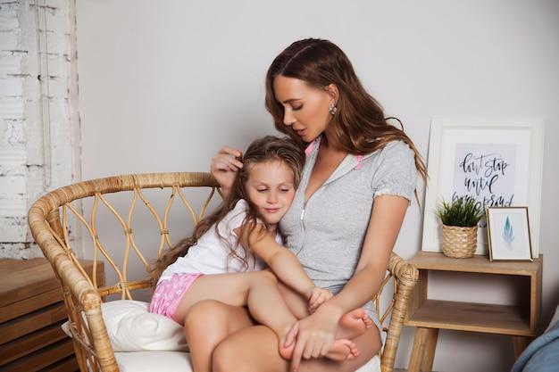 De aantrekkelijke jonge vrouw met weinig leuk meisje brengt thuis tijd samen door. gelukkig familie concept. moeder en klein kind kussen en knuffelen Premium Foto
