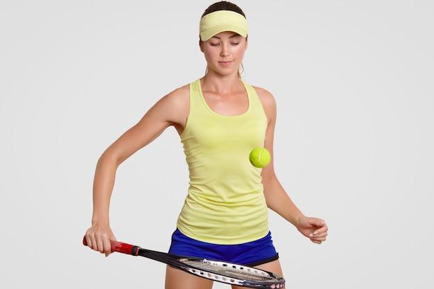 De aantrekkelijke jonge vrouwelijke professionele tennisspeler sloeg tennisbal met racket, treinen in gymnastiek, draagt hoofdband, borrels en poloshirt, heeft geconcentreerde uitdrukking, die over witte muur wordt geïsoleerd. Premium Foto