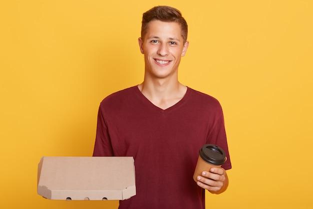 De aantrekkelijke kerel met haalt koffie en kartondoos met pizza weg Gratis Foto