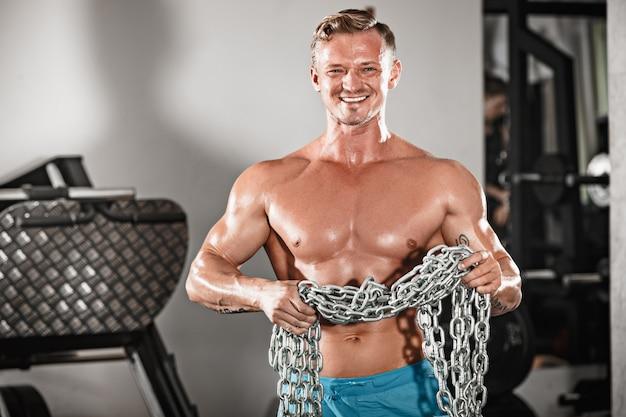 De aantrekkelijke knappe mannelijke bodybuilder die bodybuilding doen stelt in gymnastiek met ijzerkettingen Gratis Foto