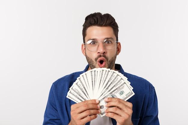 De aantrekkelijke mens houdt contant geldgeld in één hand, op geïsoleerd wit Premium Foto