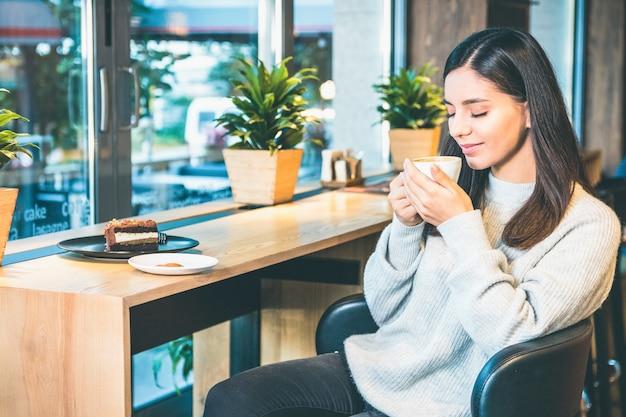 De aantrekkelijke vrouw die een kop van koffie elegant houden met ogen sloot zitting door venster Premium Foto