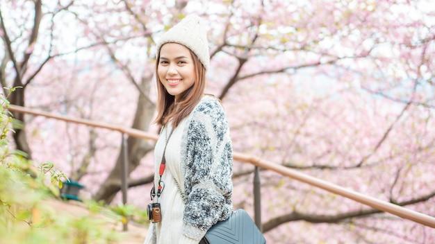 De aantrekkelijke vrouw geniet van met cherry blossom in het park Premium Foto