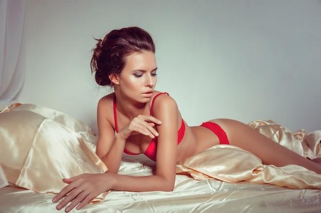De aantrekkelijke vrouw in sexy rode lingerie die in verleidelijk liggen stelt op bed Premium Foto