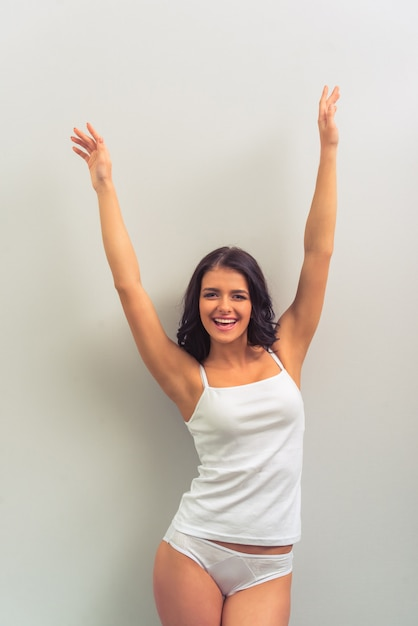 De aantrekkelijke vrouw in wit ondergoed bekijkt voorzijde. Premium Foto