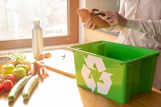 De aardappel van de vrouwenschil in recylcing mand Premium Foto