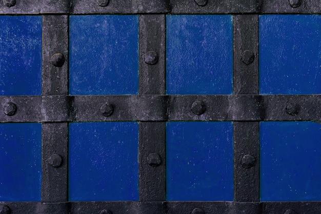 De achtergrond is geschilderd met blauwe verf met metalen balken en klinknagels. Premium Foto