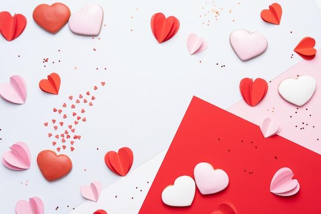 De achtergrond van de valentijnskaartendag met koekjes, rode en roze harten op pastelkleurachtergrond Premium Foto