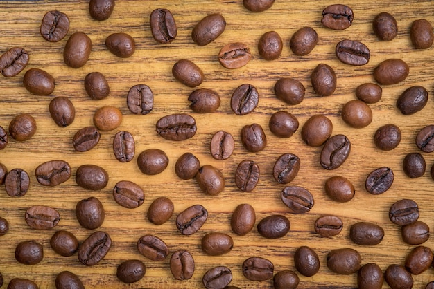 De achtergrond van gebrande koffiebonen is bruin op houten planken Premium Foto