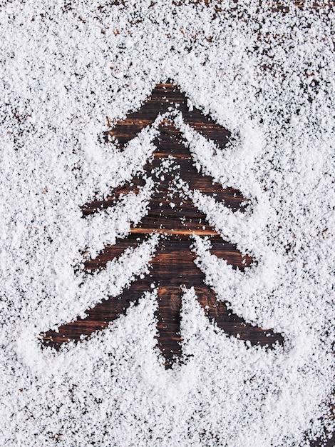 De achtergrond van het kerstmisconcept, geschilderde boom op witte sneeuw, vakantiesymbool. Premium Foto