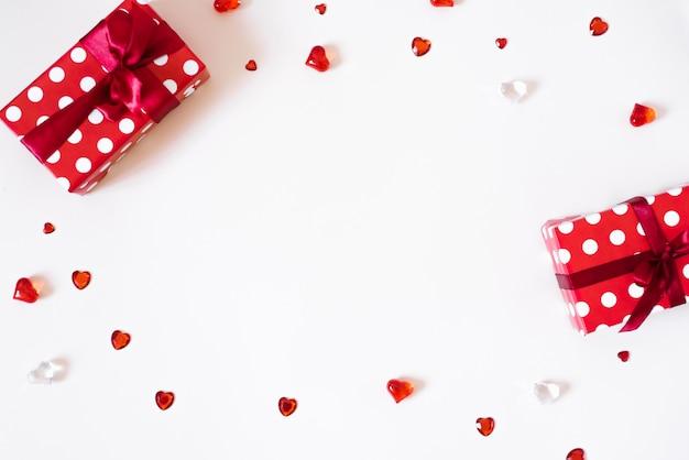 De achtergrond van valentijnsdag. geschenken met strikken, confetti, steentjes, glasharten op een lichte achtergrond. het concept van valentijnsdag Premium Foto