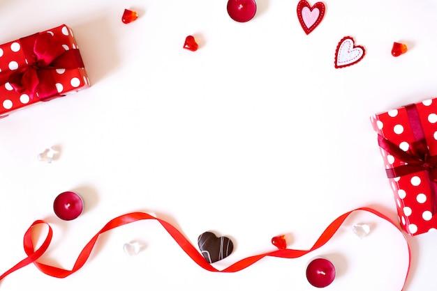 De achtergrond van valentijnsdag. geschenken met strikken, kaarsen, confetti, rood satijnen lint, harten op een lichte achtergrond. het concept van valentijnsdag Premium Foto