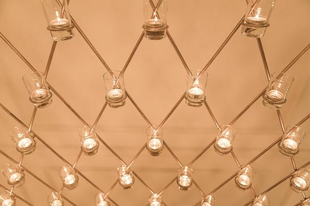 De achtergrond van veel kleine gouden kaarsen Premium Foto