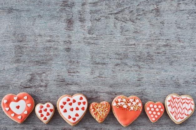 De achtergrond van verfraaid met suikerglazuur en de verglaasde koekjes van de hartvorm op grijze vlakke achtergrond, lag. valentijnsdag eten concept Premium Foto