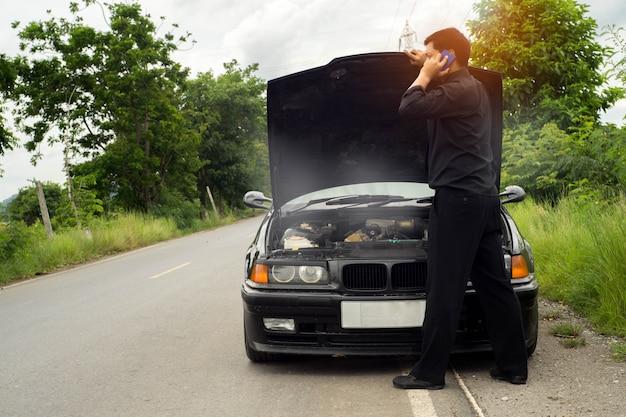 De achterkant van de technicus houdt de schroevendraaier voor reparatie auto's, gebroken auto met rook Premium Foto