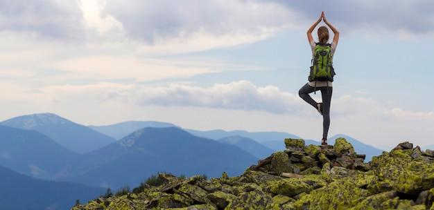 De achtermening van jong slank toeristenmeisje met rugzak die zich op één been in yoga bevinden stelt op rotsachtige bovenkant op heldere blauwe ochtendhemel en mistige bergenachtergrond. toerisme, reizen en klimmen concept. Premium Foto